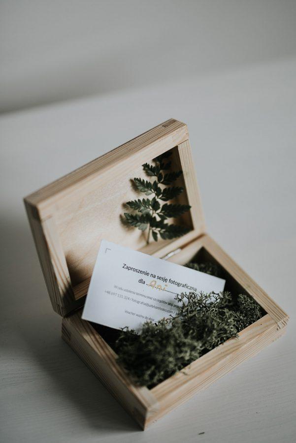 Zdjęcie pokazuje sposób zapakowania vouchera na naturalną sesję zdjęciową.